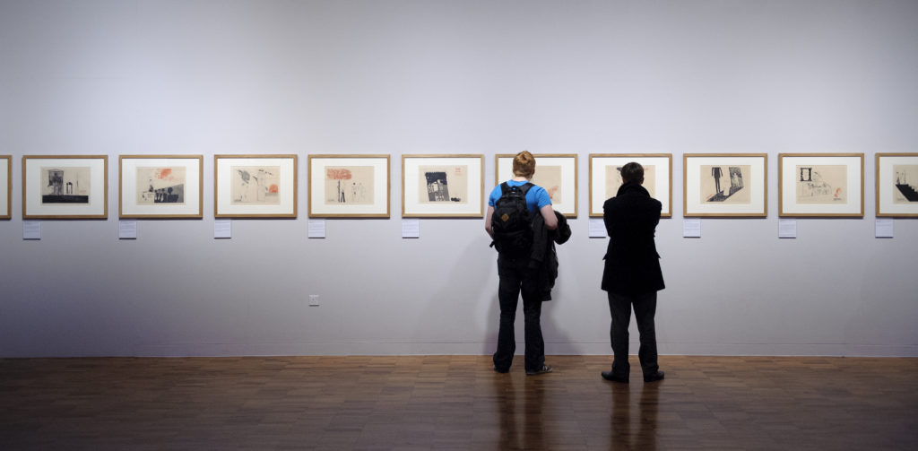 Two people looking at framed illustrations on a wall in an exhibition in an art gallery