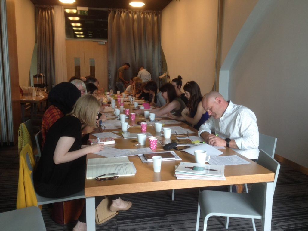 A workshop with people sitting around a large desk writing