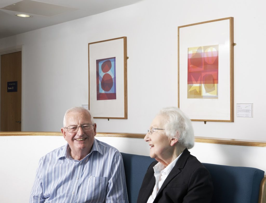 Two people in a health centre waiting area with two paintings on the wall behind them