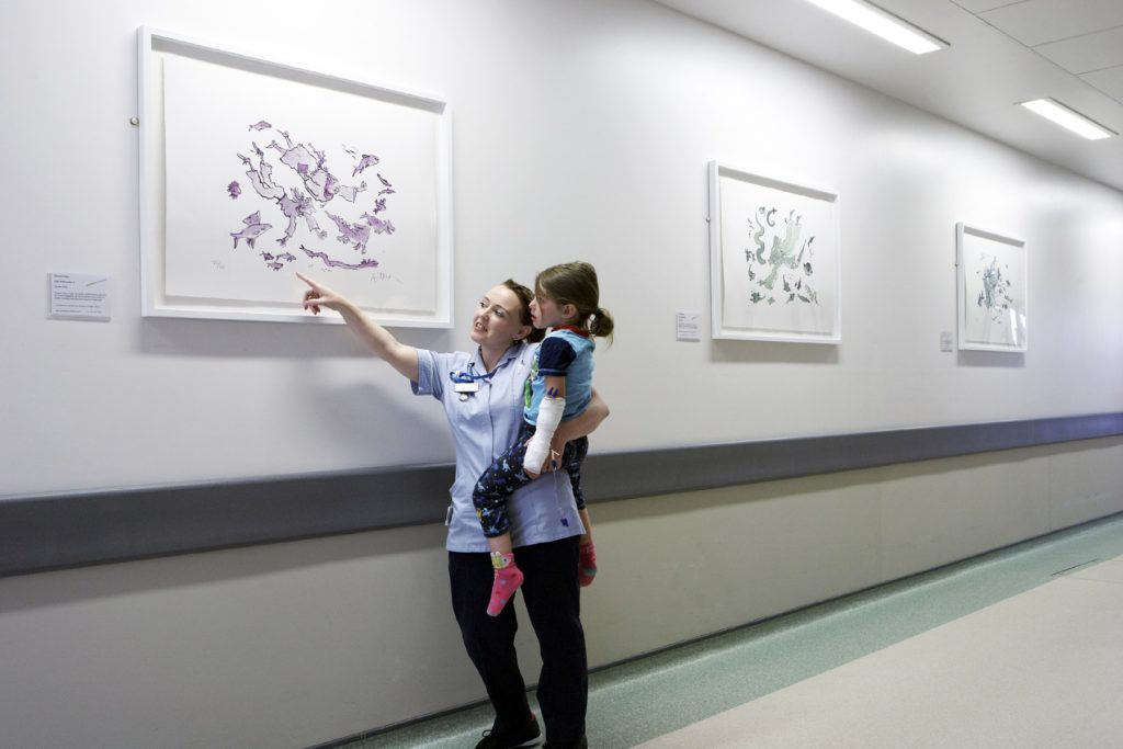 A healthcare professional carrying a child and looking at a Quentin Blake artwork on the wall in a hospital